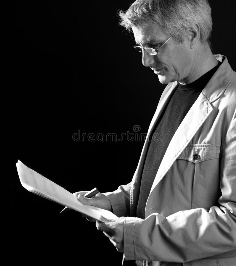 Businessman reading at work, senior gray hair royalty free stock image