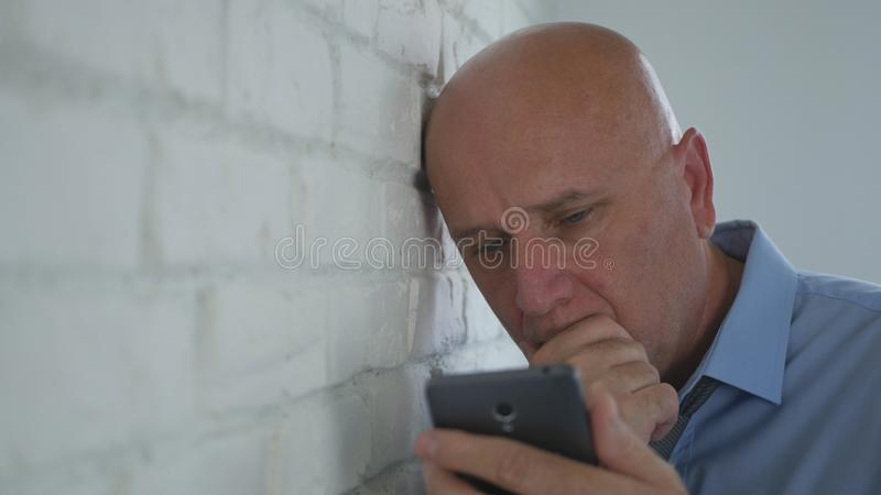 Businessman Reading Worried and Disappointed Financial Bad News on Mobile Phone.  stock photography