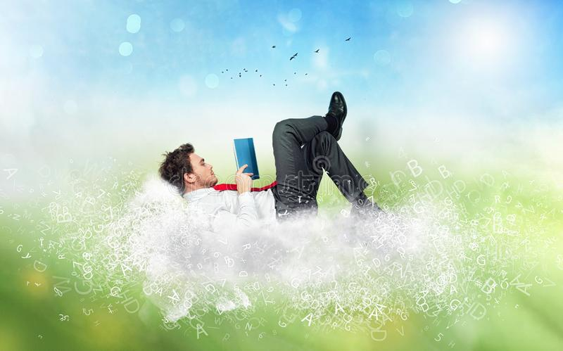 Businessman reads a book over a cloud made of letters. Concept of relax and imagination stock photography