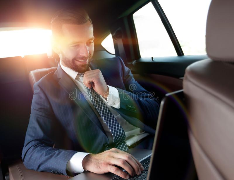 Businessman reads information on laptop while sitting in car stock image