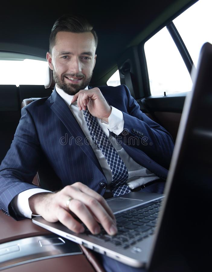 Businessman reads information on laptop while sitting in car stock photo