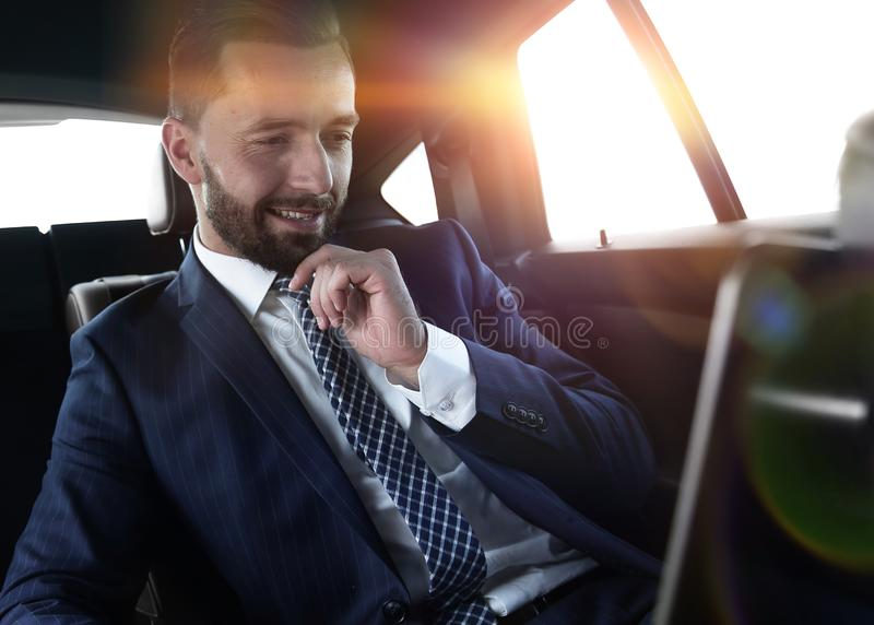 Businessman reads information on laptop while sitting in car royalty free stock image