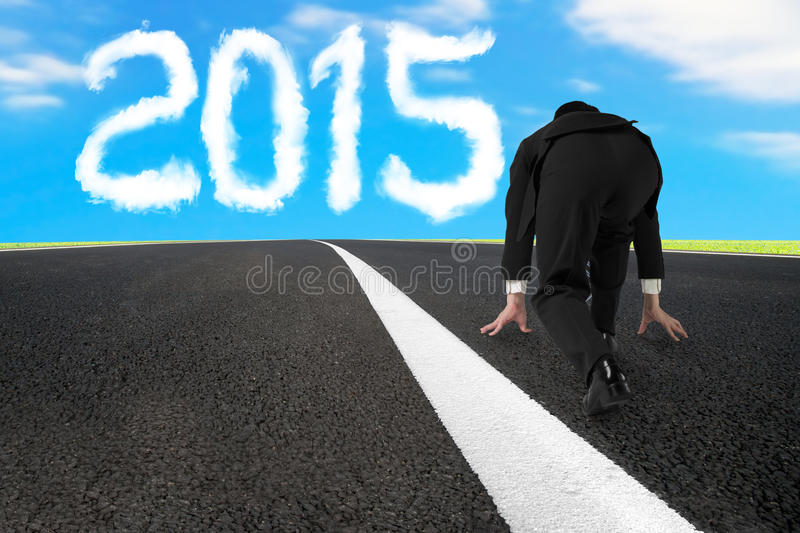 Businessman ready to run on asphalt road with 2015 cloud royalty free stock image