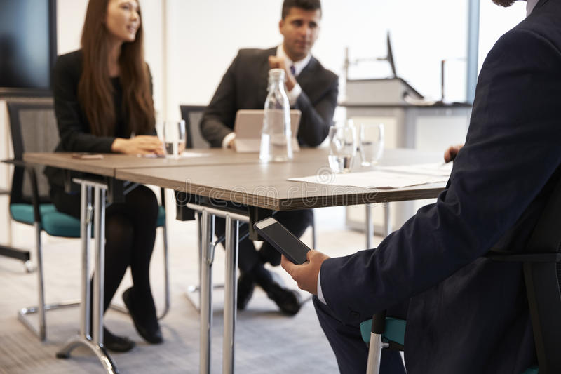 Businessman Receiving Text Message During Meeting stock photography