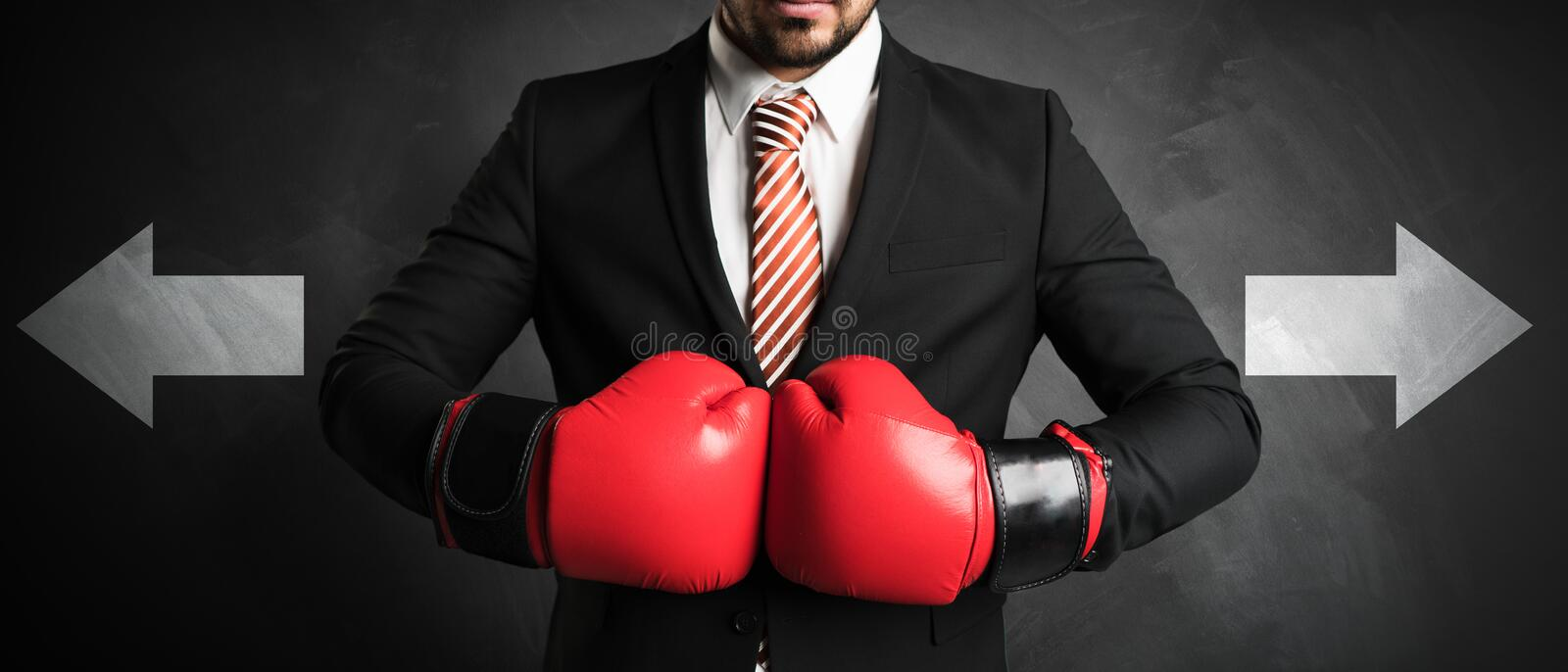Businessman with red boxing gloves. In front of a chalkboard with arrow symbolizing a tough decision stock images