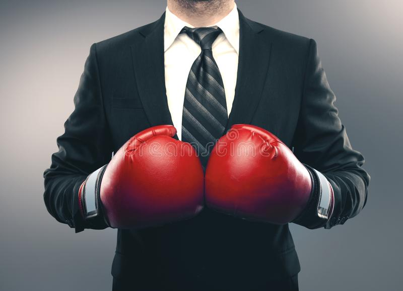 Businessman in red boxing gloves. Isolated on gray background. Business challenge concept stock image