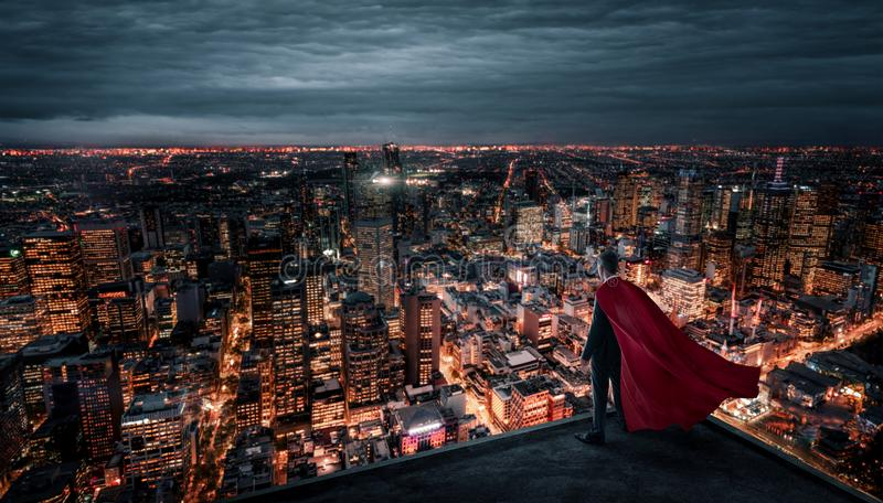 Businessman with red cape standing on the rooftop royalty free stock photo
