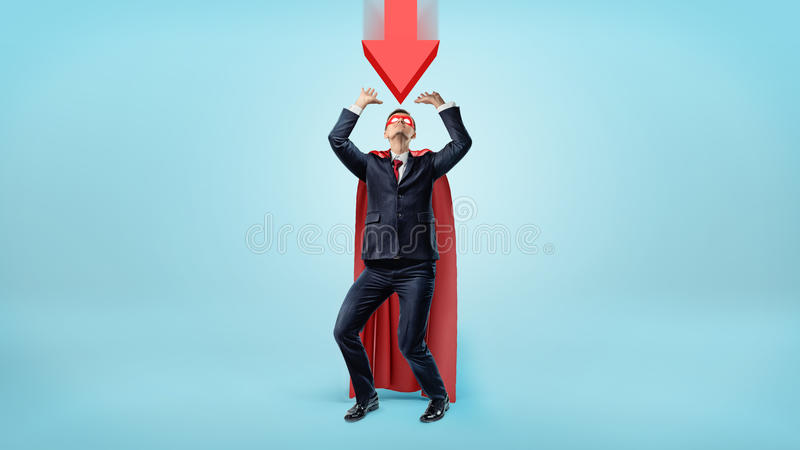 A businessman in a red cape and a mask cowering under a large red arrow pointing down at him. Business troubles. Unexpected problems. Recession royalty free stock photo