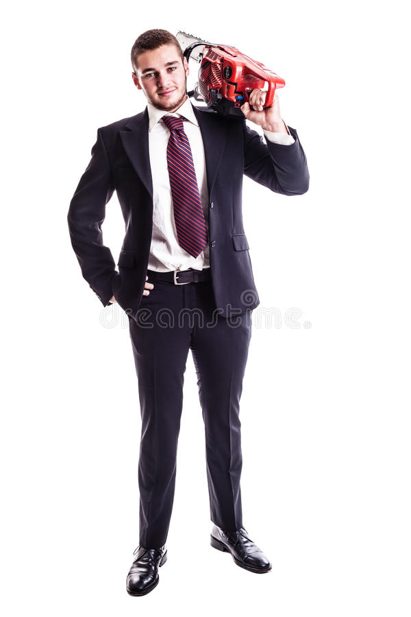 Businessman with a red chainsaw. A young businessman holding a red chainsaw isolated over a white background royalty free stock photos