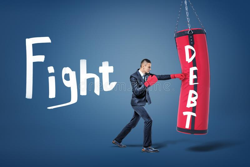 A businessman in red gloves hits a large red boxing bag with a word Debt written on it. stock image