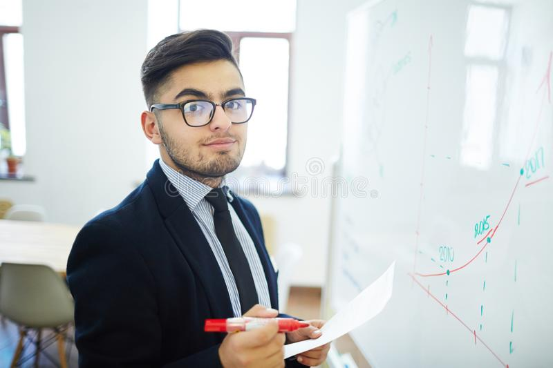 Successful financier. Businessman with red highlighter and paper standing by whiteboard with drawn graph of financial rate royalty free stock photography