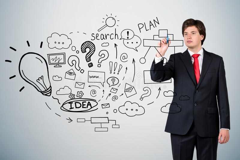 Businessman with red tie and startup idea sketch on gray wall. Young businessman wearing red tie is standing near gray wall with startup idea sketch on it stock photography