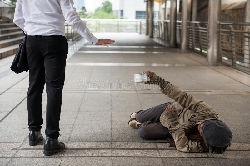 Businessman refuse giving money to homeless man. Businessman raise hand to refuse giving money to old handicappe homeless man lying on city walk floor. Poverty royalty free stock photography
