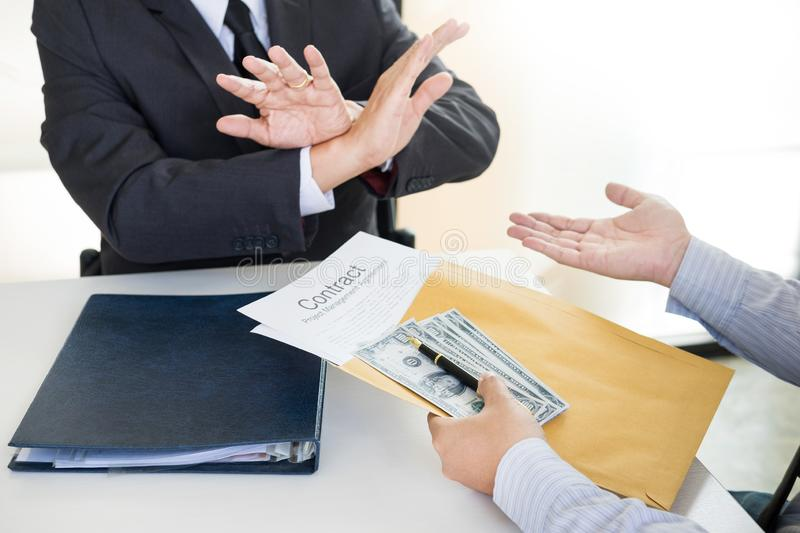 Businessman refuses to receive money that come with agreement paper - no bribery and corruption concept. Businessman refuses to receive money that come with stock photography