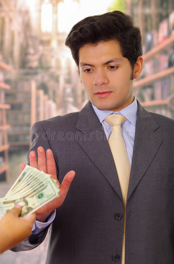 Businessman refuses to take bribe. Smart young businessman refuses to take bribe royalty free stock photo