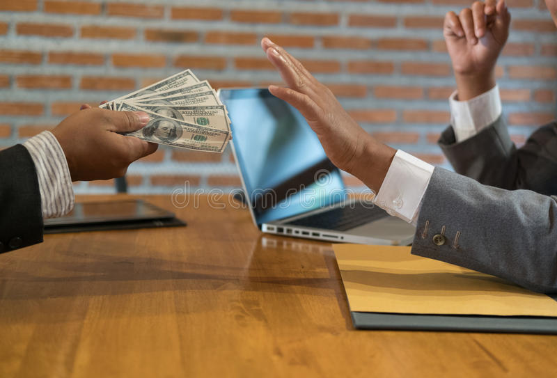 Businessman rejecting money cash banknote from a man. honest business people in suit refuse to take the bribe - anti bribery, cor royalty free stock photos