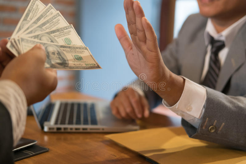 Businessman rejecting money cash banknote from a man. honest business people in suit refuse to take the bribe - anti bribery, cor. Ruption, venality concept royalty free stock photo
