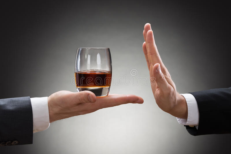Businessman rejecting whisky offered by businessperson. Close-up Of Businessman Hand Reject A Glass Of Whisky Offered By Businessperson royalty free stock images