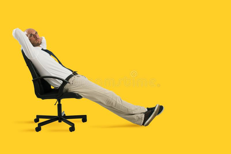 Businessman relax and think sitting on a chair. Yellow background royalty free stock image
