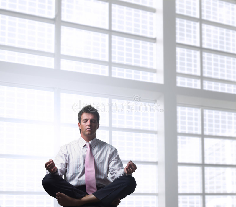 Businessman relaxing. Handsome businessman is relaxing in the office, sitting in a traditional yoga lotus position stock images