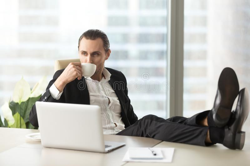 Businessman relaxing and drinking coffee at workplace in office. stock photo