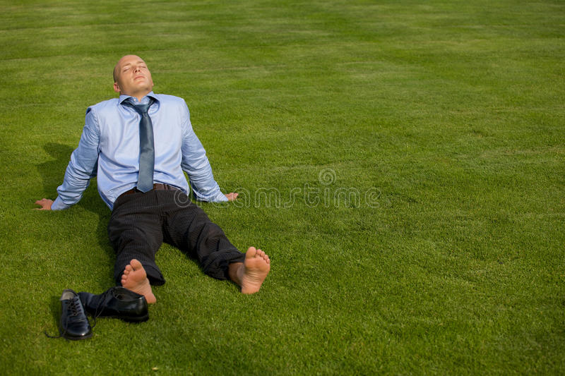 Businessman relaxing in park stock photos