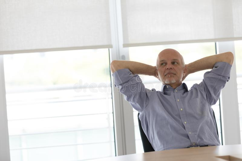 Businessman relaxing with hands behind his head royalty free stock photography
