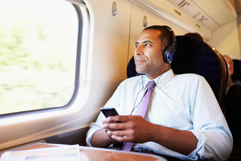 Businessman Relaxing On Train Listening To Music. Looking Out Of Window