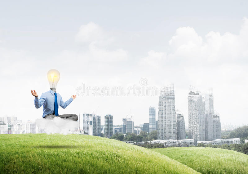 Businessman relaxing and waiting for inspiration. Businessman sitting in lotus pose and light bulb instead of his head royalty free stock photos