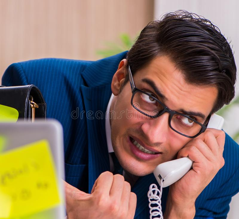 Businessman with reminder notes in multitasking concept. The businessman with reminder notes in multitasking concept stock photography