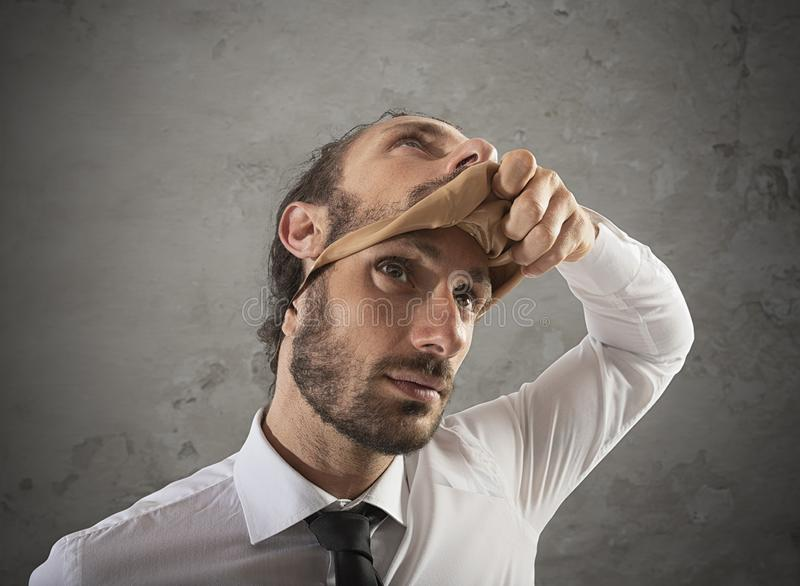 Businessman that removes the mask. Concept of falsity stock images