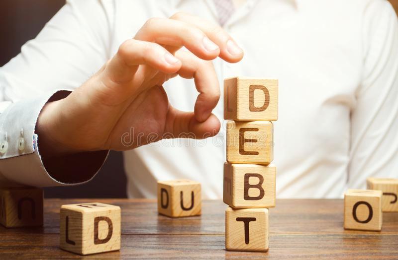 Businessman removes wooden blocks with the word Debt. Reduction or restructuring of debt. Bankruptcy announcement. Refusal to pay royalty free stock photography