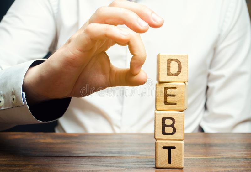 Businessman removes wooden blocks with the word Debt. Reduction or restructuring of debt. Bankruptcy announcement. Refusal to pay stock images