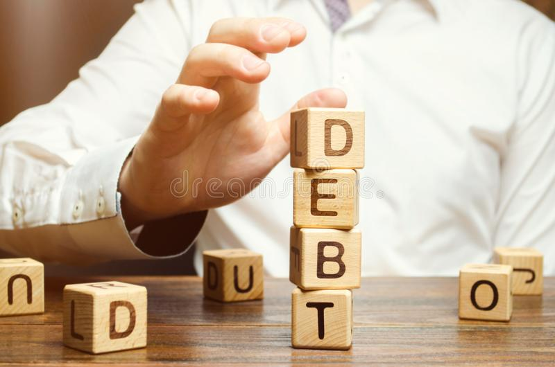 Businessman removes wooden blocks with the word Debt. Reduction or restructuring of debt. Bankruptcy announcement. Refusal to pay. Debts or loans and invalidate royalty free stock image