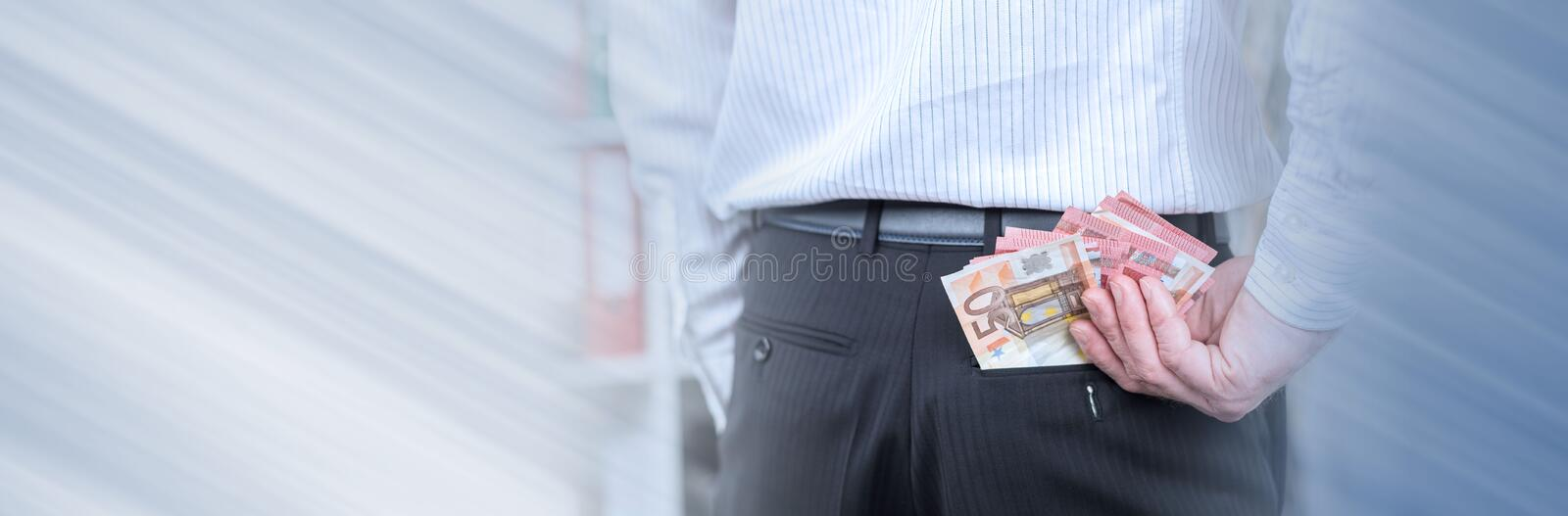 Businessman removing banknotes from his pocket; panoramic banner. Businessman removing euro banknotes from his pocket; panoramic banner royalty free stock photos