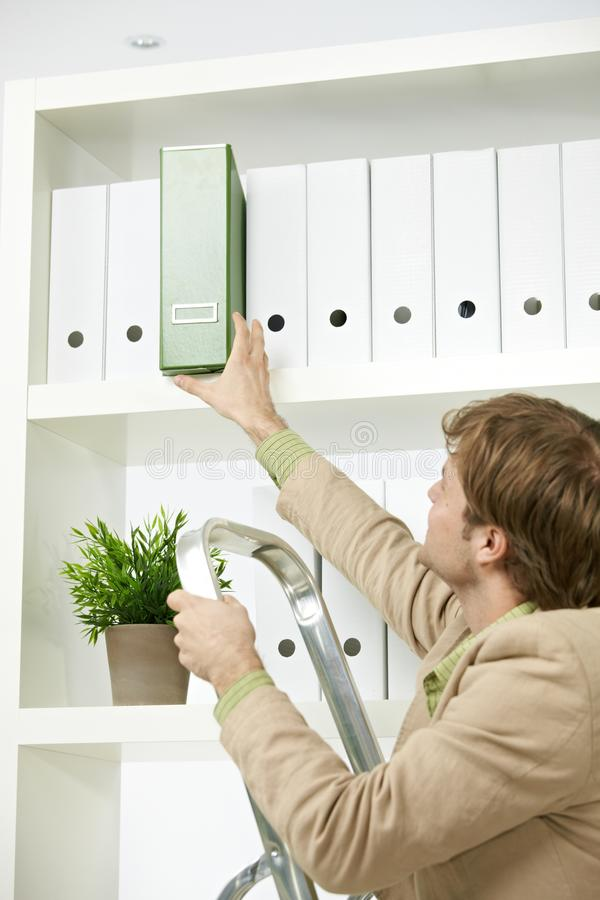 Businessman removing green folder from shelf. Businessman on ladder removing green folder from shelf royalty free stock image