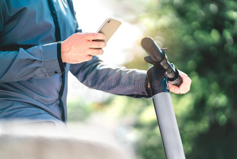 Businessman renting electric kick scooter with smartphone in city park. Hipster man using smart mobile phone rental service. stock photo