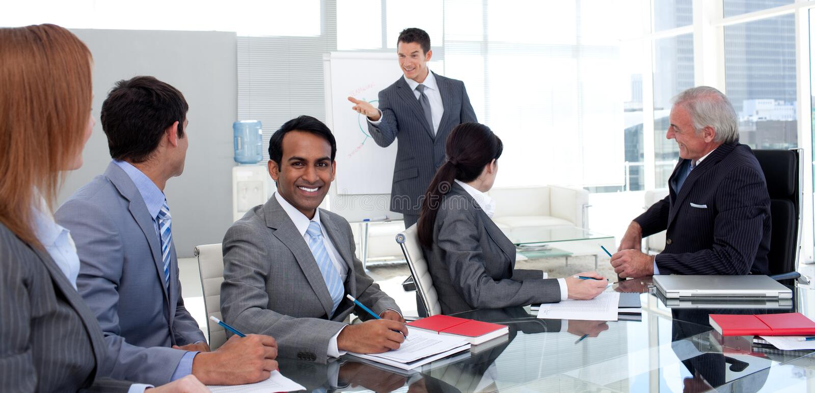 Businessman reporting sales figures to his team