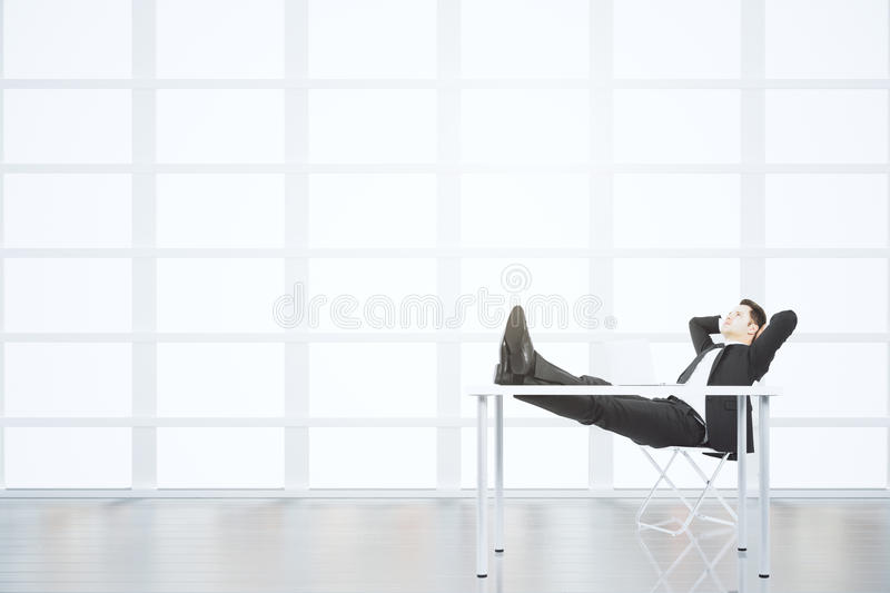 Businessman resting on a chair in light empty loft office stock photos