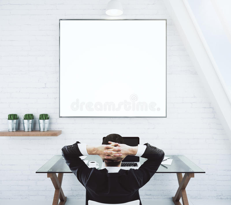 Businessman resting on a chair and looking at blank white picture frame on white brick wall, mock up stock photos