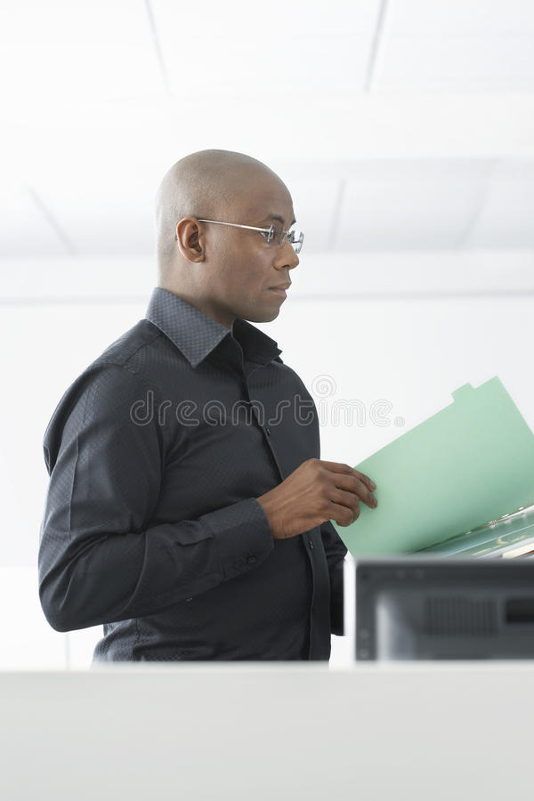 Download Businessman Reviewing File At Computer Desk Stock Photo - Image: 31833180