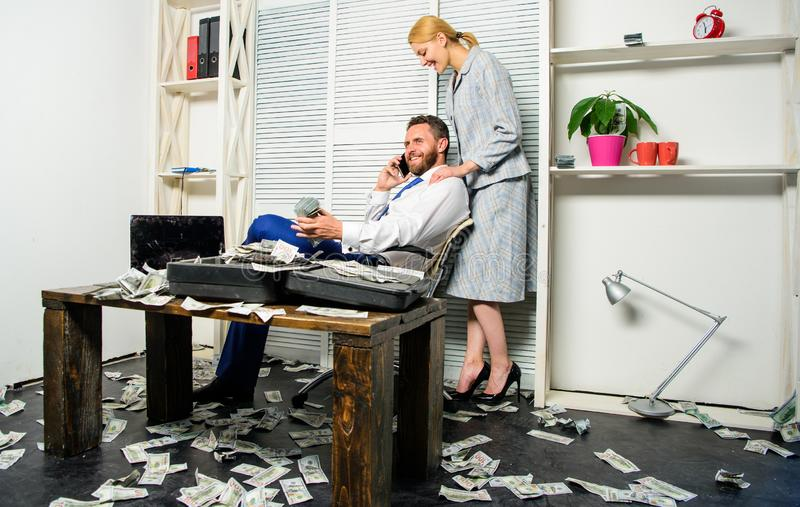 Businessman rich bearded guy sit office with lot of cash money. Man successful businessman phone conversation while. Assistant do shoulders massage. Office royalty free stock photography
