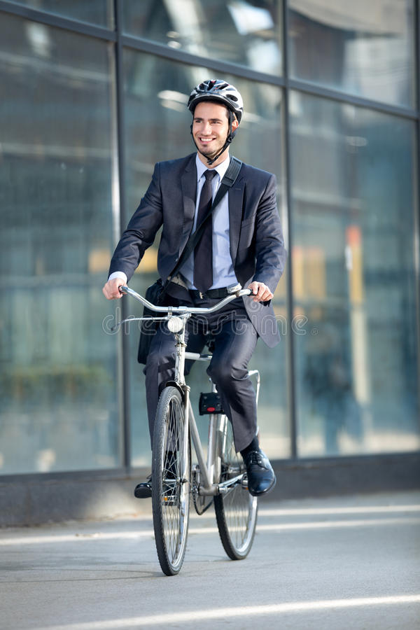 Businessman riding bicycle by building. Young businessman riding bicycle by building on street royalty free stock image