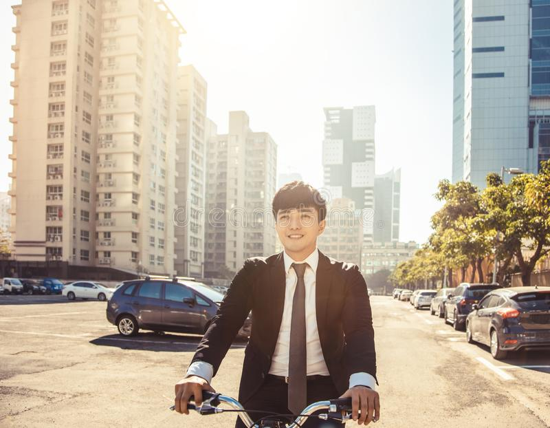 Businessman riding bicycle to work on urban street at morning stock photography