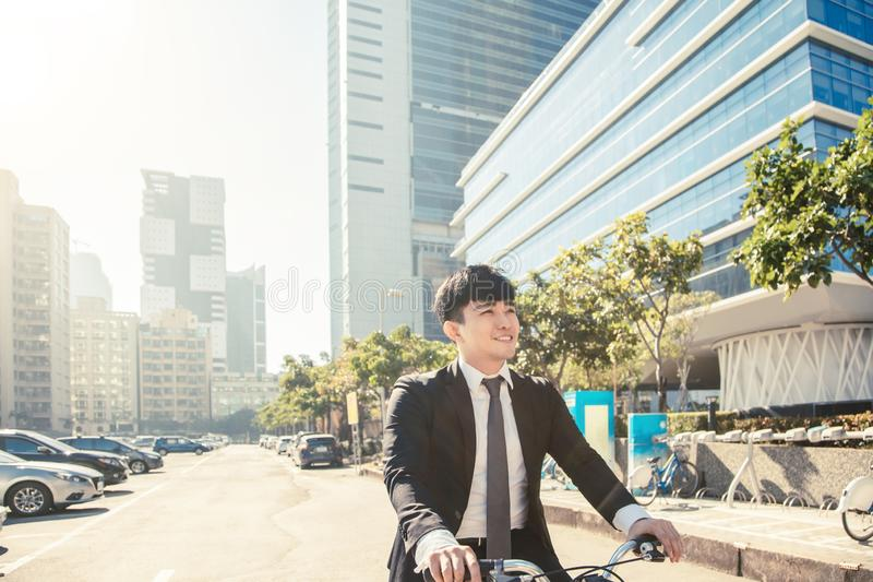 Businessman riding bicycle to work on urban street at morning royalty free stock photography