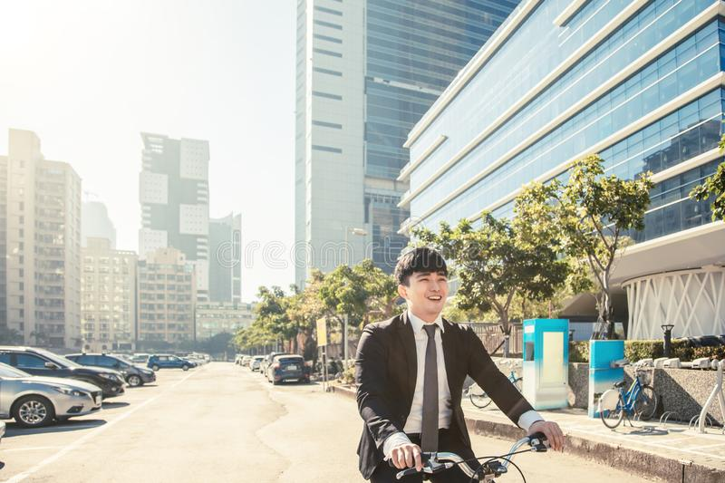 Businessman riding bicycle to work on urban street at morning royalty free stock photos