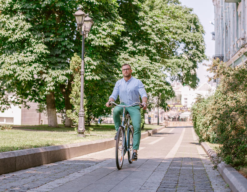 Businessman riding bicycle to work on urban street in morning. stock photography