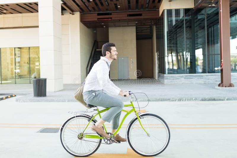 Businessman Riding Bike To Stay Fit And Pollution Free stock photo
