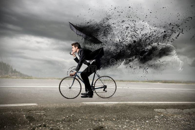 Businessman riding a bike with an umbrella stock photo
