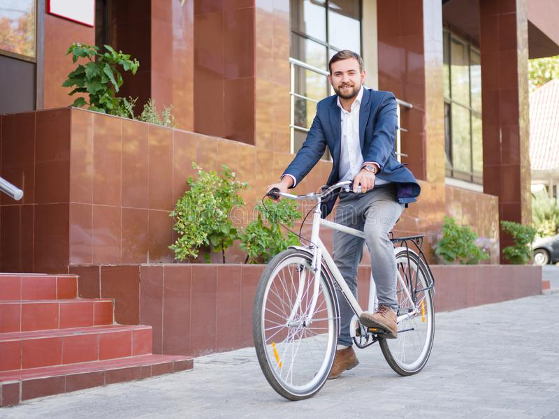 Businessman is riding his white bike down the street royalty free stock photos